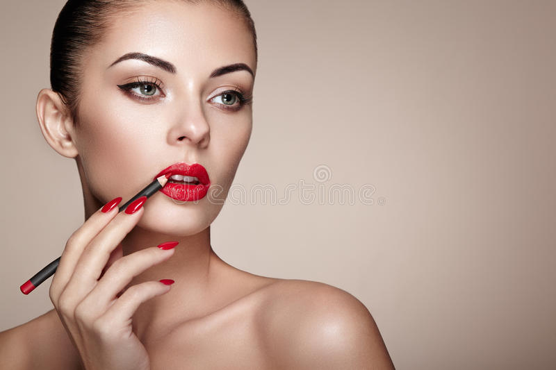 Beautiful woman paints lips with lipstick. Beautiful woman face. Makeup detail. Beauty girl with perfect skin. Red lips and nails manicure royalty free stock photos