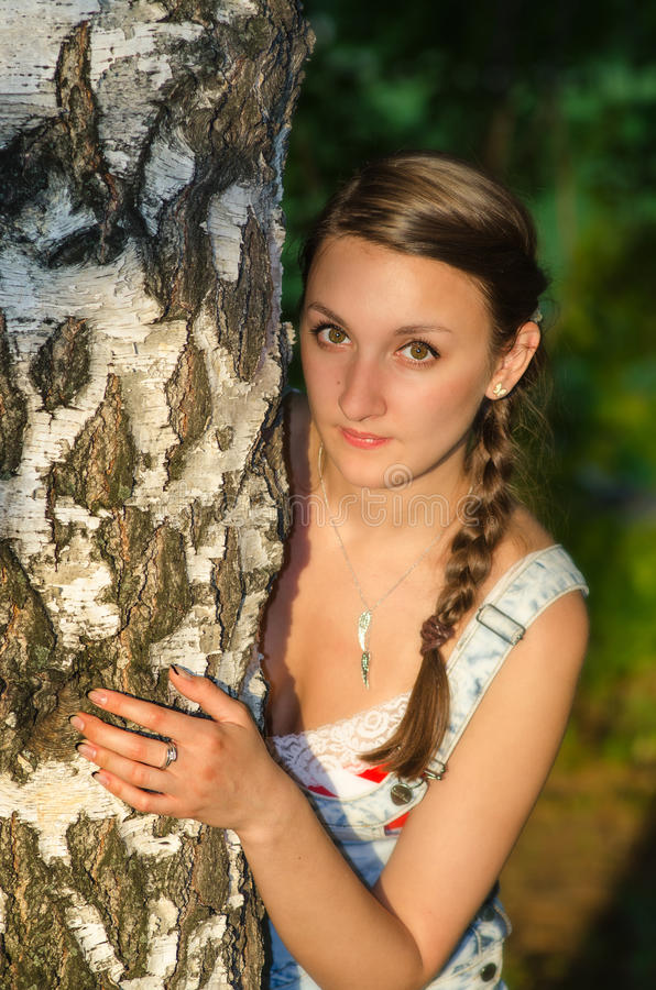 Beautiful young female near the tree stock images