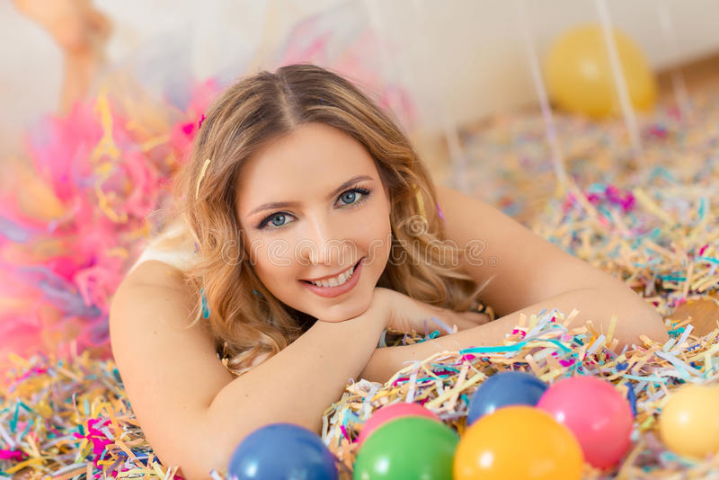 Beautiful woman party portrait. Happy smiling woman celebrate birthday laing on the floor all in confetti royalty free stock image