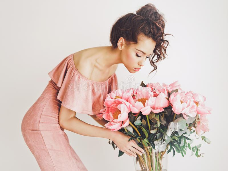 Beautiful woman with peonies. Lifestyle photo of beautiful young woman with pink peonies. Bouquet as gift. Emotions of happiness and joy. Valentines day. Mothers royalty free stock photos