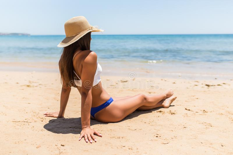 Beautiful woman with perfect body lying down on the beach, wearing stylish hat, tanning on a beach resort, enjoying summer vacatio royalty free stock photos