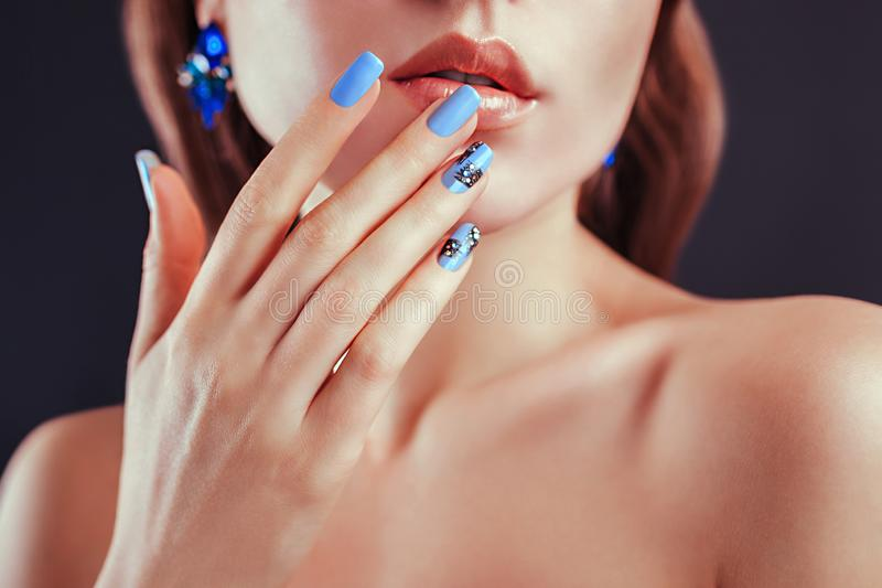Beautiful woman with perfect make-up and blue manicure wearing jewellery. Nail design. Beauty and fashion concept. stock photos