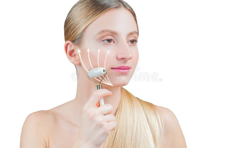 Beautiful woman with perfect skin and arrows on face, getting lifting massage using roller massager. Anti-aging treatment and face lift. Beautiful woman with stock photos