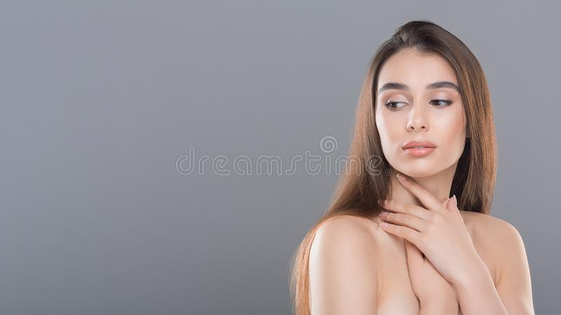 Beautiful woman with perfect skin and bare shoulders. Looking aside at empty space on a gray background stock photo
