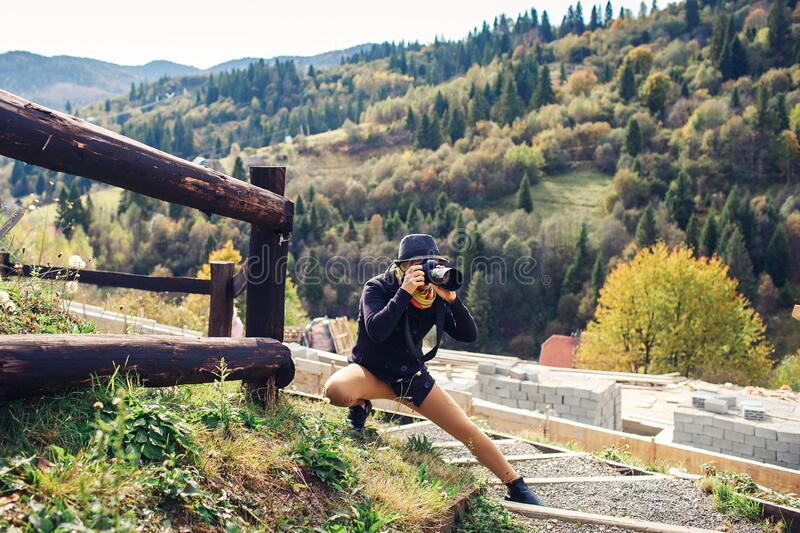 Beautiful woman photographs nature on the mountain in autumn.  royalty free stock image