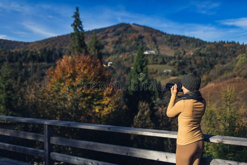 Beautiful woman photographs nature on the mountain in autumn.  royalty free stock photography