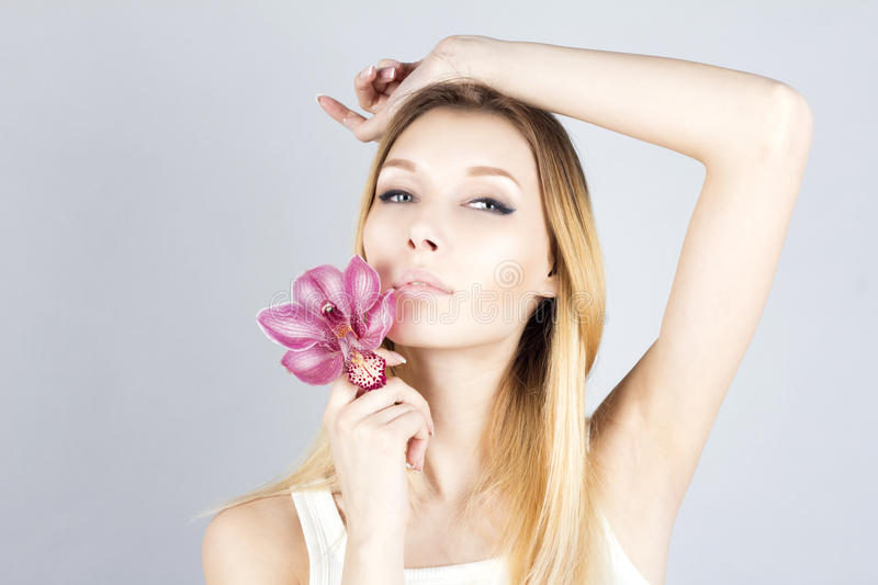 Beautiful woman with pink flower and her hand raised. Waxing armpit. Epilation result. royalty free stock photos