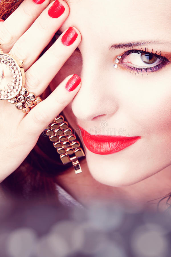 Beautiful woman with pink lips and watch. Face of a beautiful young woman with bright pink lipstick and glitter nailpolish holding a watch with a smile royalty free illustration