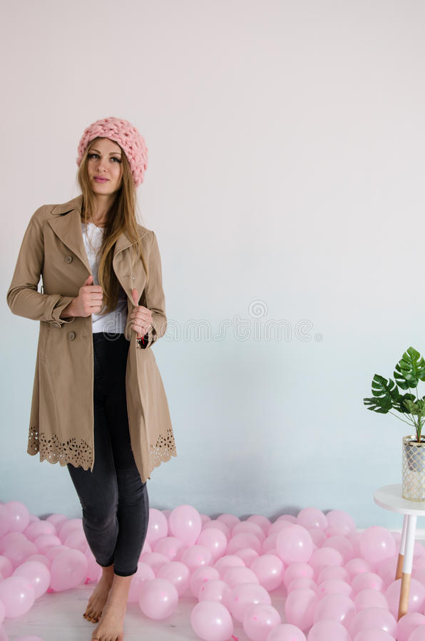 Beautiful woman in pink merino wool hat with balloons on floor stock photography