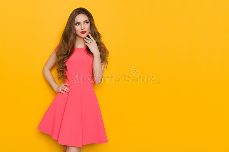 Beautiful Woman In Pink Mini Dress And Turquoise Ring Is Looking Away royalty free stock photo