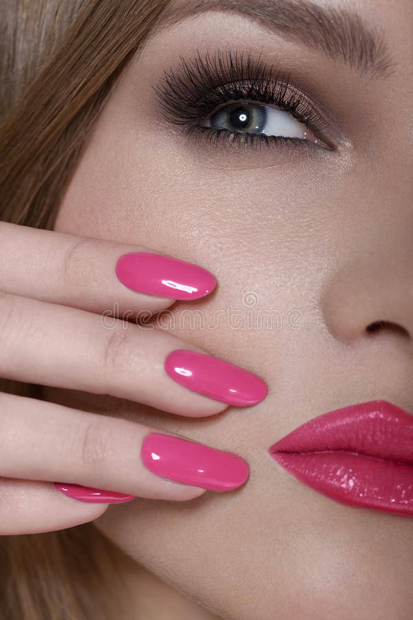 Beautiful Woman With Pink Nails and Luxury Makeup. Red Lips and Long Eyelashes stock image