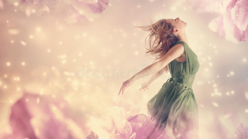 Beautiful woman in a pink peony flower fantasy stock photo