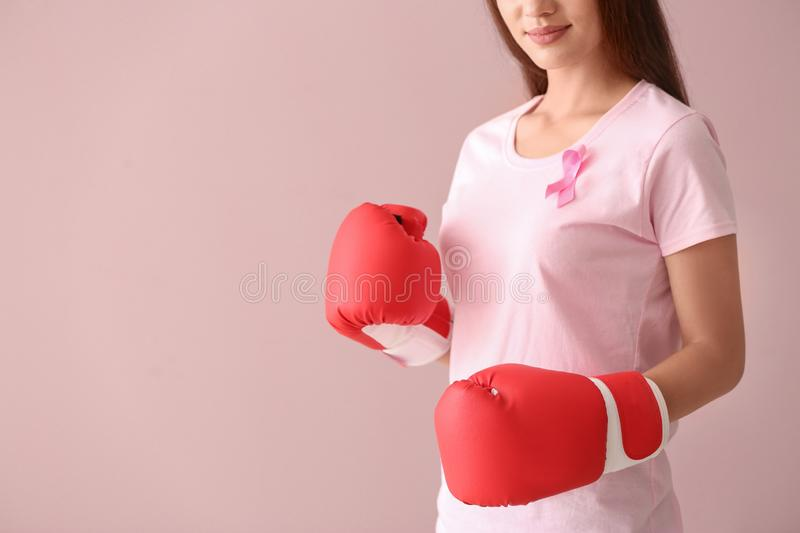 Beautiful woman with pink ribbon and boxing gloves on color background. Breast cancer concept royalty free stock photos