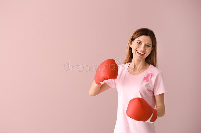 Beautiful woman with pink ribbon and boxing gloves on color background. Breast cancer concept stock photo