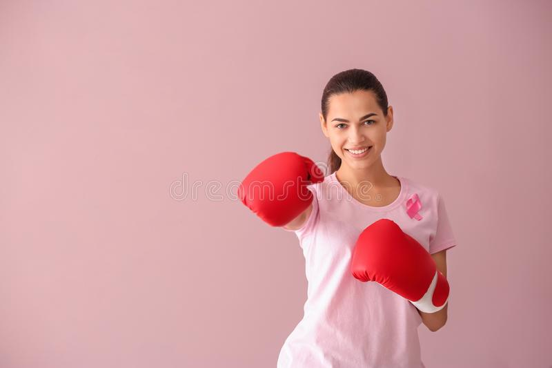Beautiful woman with pink ribbon and boxing gloves on color background. Breast cancer concept royalty free stock images