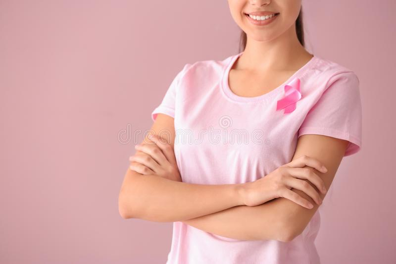 Beautiful woman with pink ribbon on color background. Breast cancer concept royalty free stock image