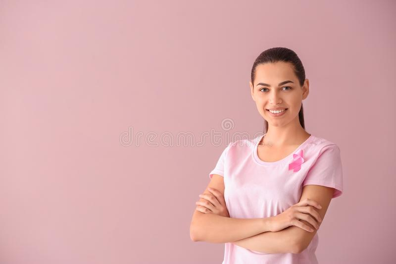 Beautiful woman with pink ribbon on color background. Breast cancer concept stock image