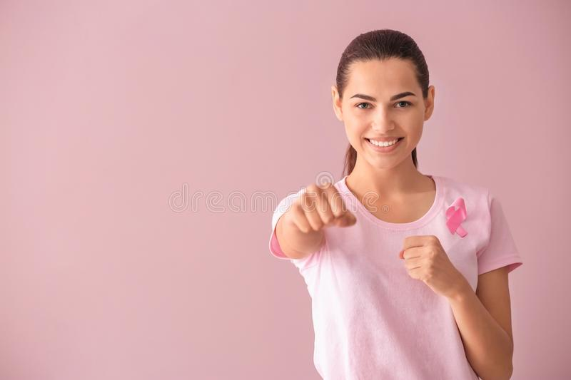 Beautiful woman with pink ribbon on color background. Breast cancer concept stock images