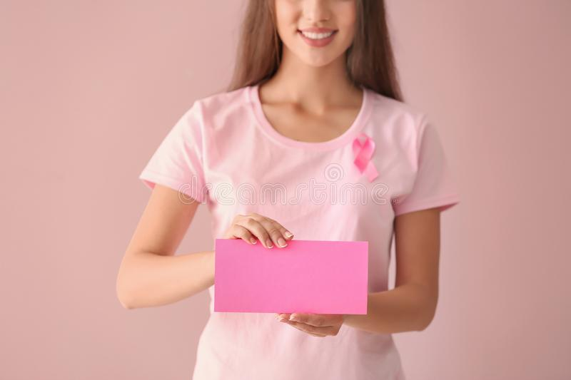 Beautiful woman with pink ribbon holding card on color background. Breast cancer concept royalty free stock photos