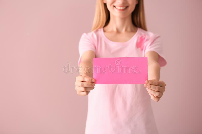 Beautiful woman with pink ribbon holding card on color background. Breast cancer concept royalty free stock images