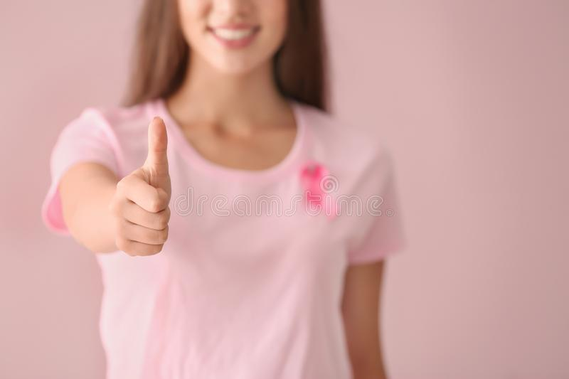 Beautiful woman with pink ribbon showing thumb-up gesture on color background. Breast cancer concept royalty free stock photos