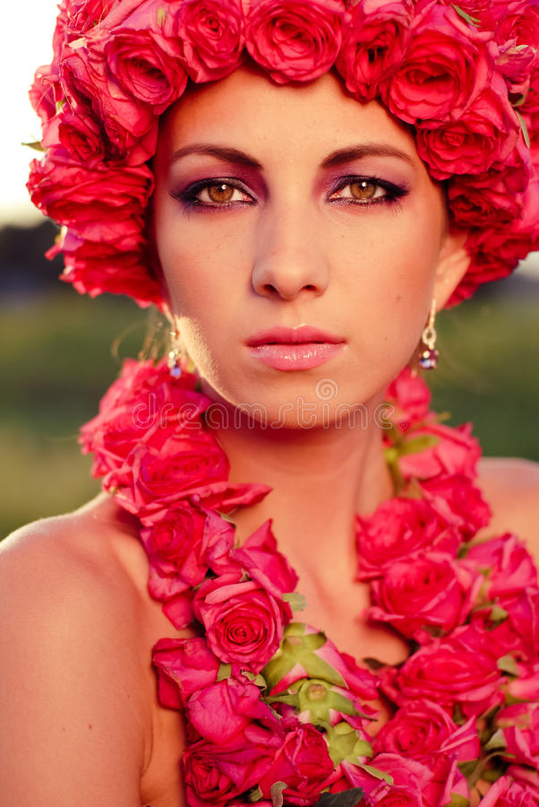 Beautiful woman & pink roses crown with garland. Young beautiful woman with pink roses crown and garland outdoors closeup portrait royalty free stock image