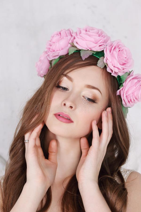 Beautiful woman in pink roses wreath with long hair. Poses in white studio stock image
