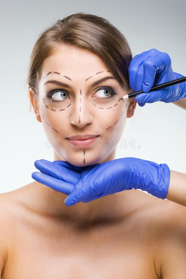 Beautiful woman with plastic surgery, depiction, plastic surgeon hands royalty free stock photos