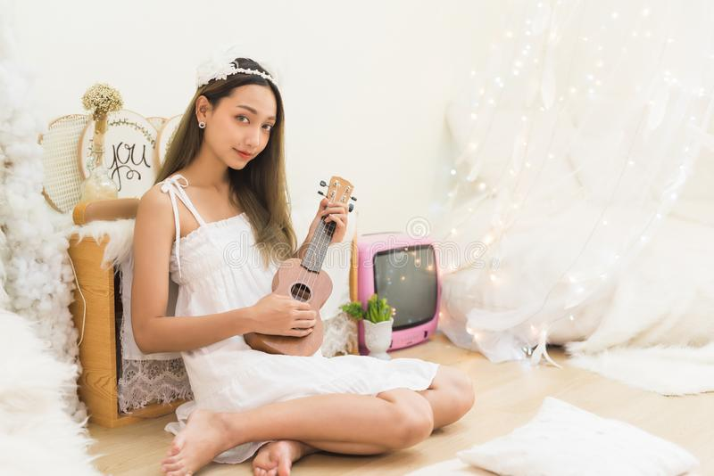 Beautiful woman play ukulele acoustic song stock images