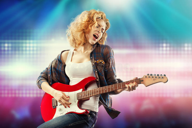 Beautiful woman playing the guitar. Portrait of young beautiful woman playing the guitar. Happiness concept royalty free stock photography