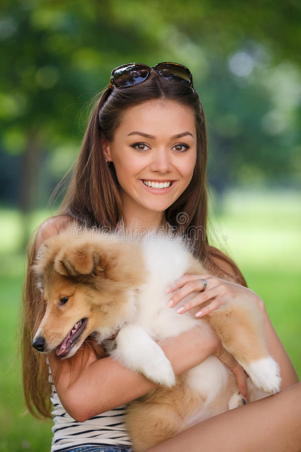 Beautiful woman playing in the park with a puppy collie. Woman beautiful young happy with long dark hair in striped sweater holding collie dog. Young woman stock photography