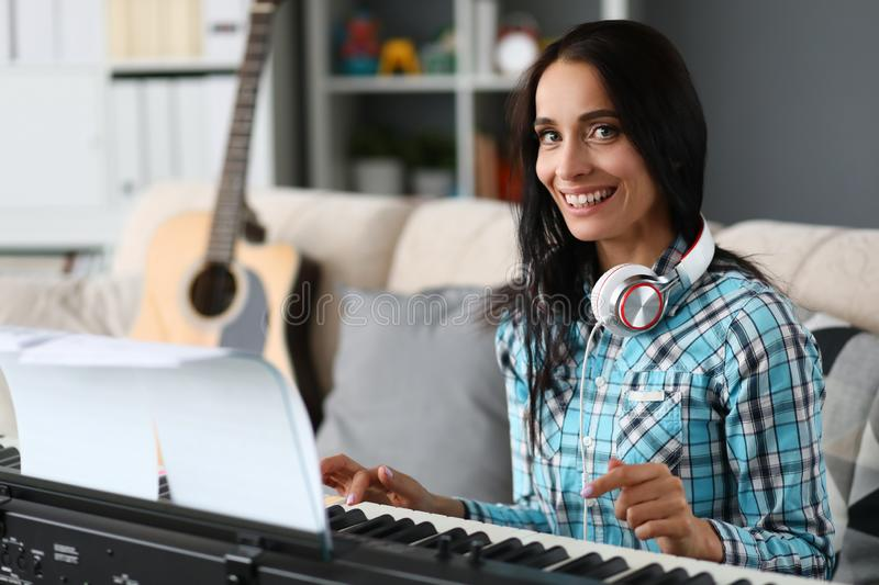 Beautiful woman playing piano on background stock images