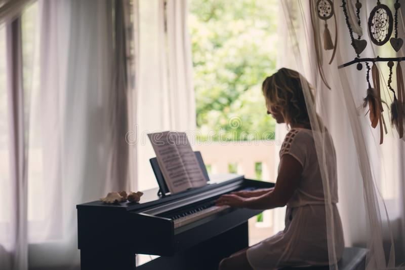 Beautiful woman playing piano stock images