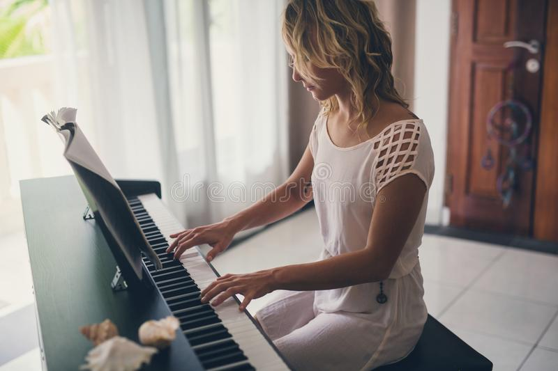 Beautiful woman playing piano. Inside of house with white curtains royalty free stock photos