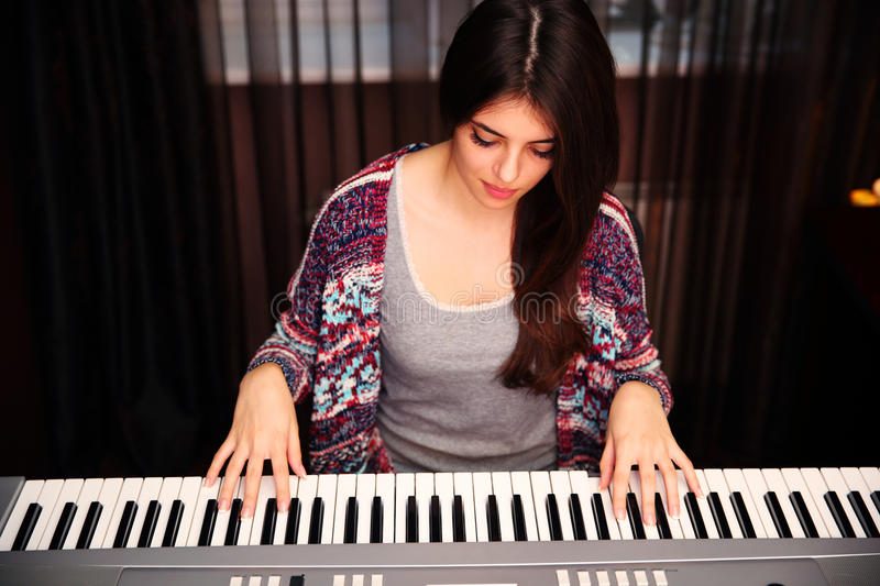 Beautiful woman playing on piano. Young beautiful woman playing on piano at home royalty free stock photos
