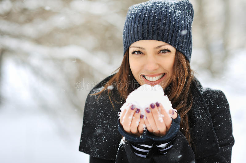 Beautiful woman playing with snow in park stock photos