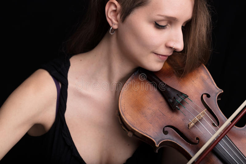 Beautiful woman playing violin studio portrait on black. Young beautiful woman violinist player playing her instrument on her shoulder holding bow. portrait in a royalty free stock photos
