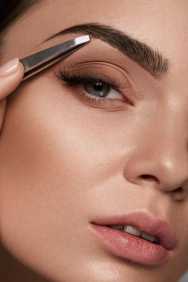 Beautiful Woman Plucking Eyebrows. Beauty Brows Correction royalty free stock image