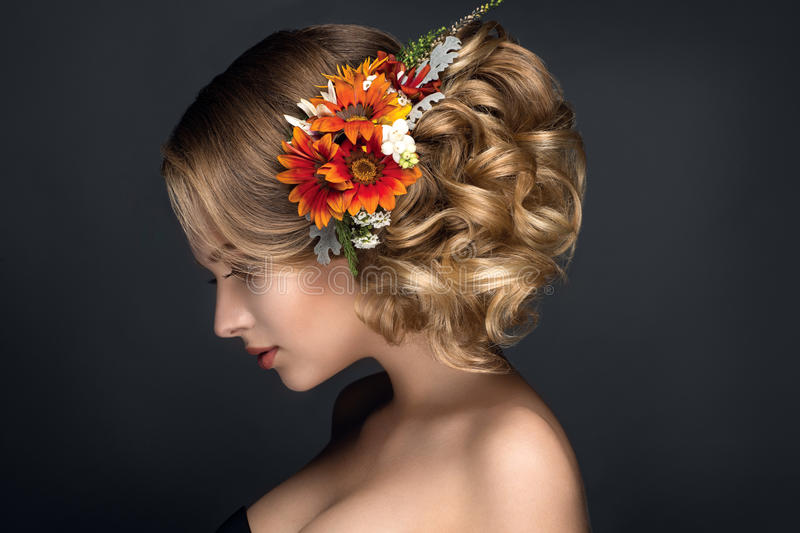Beautiful woman portrait with autumn flowers in hair. Beautiful woman portrait on black background with autumn flowers in hair royalty free stock photography