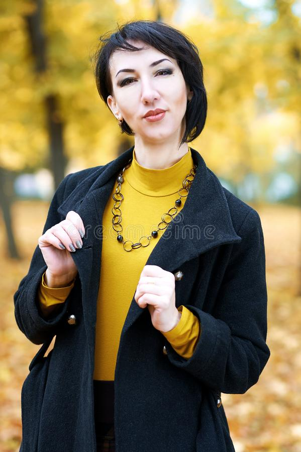 Beautiful woman portrait in autumn outdoor, yellow leaves and trees on background, fall season royalty free stock images