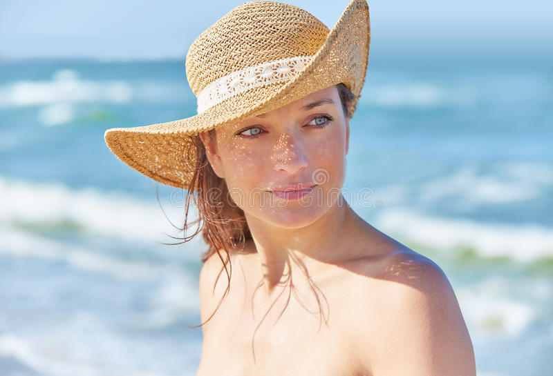 Beautiful woman portrait on the beach. With hat royalty free stock images