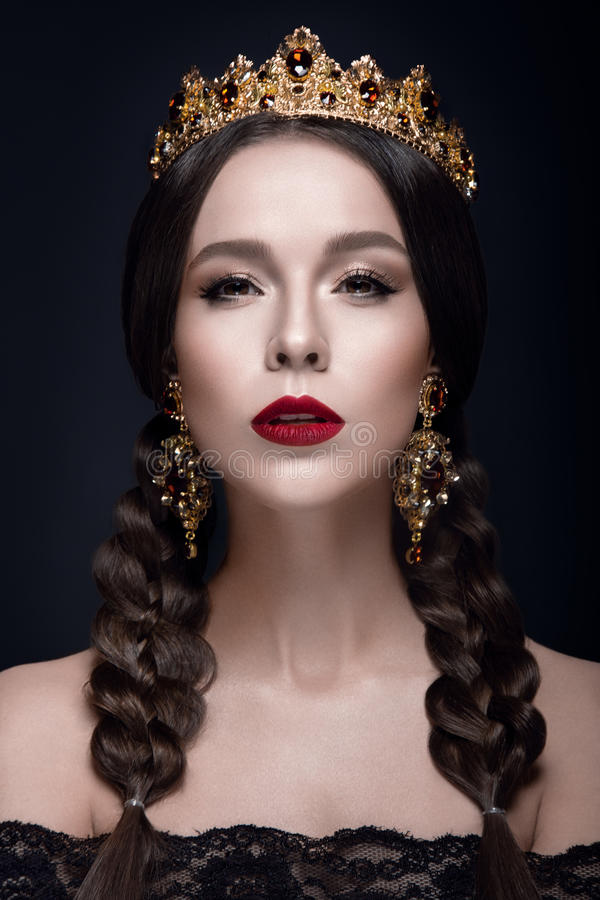Beautiful woman portrait with crown and earrings. The queen royalty free stock image