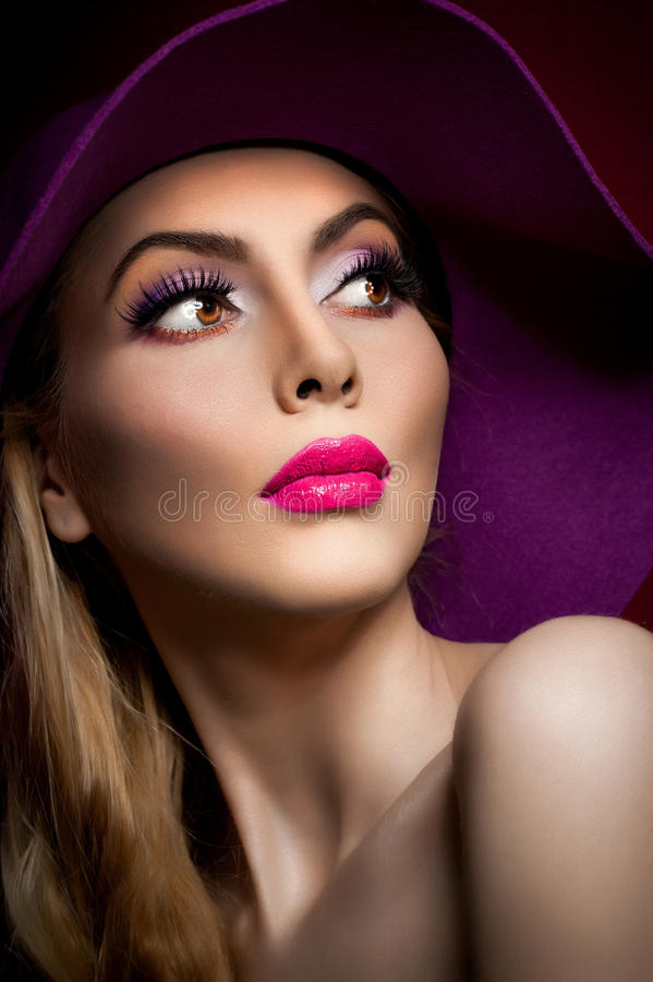 Beautiful woman portrait. Fashion art photo. Beautiful young model with mauve hat on colored background, studio shot stock images