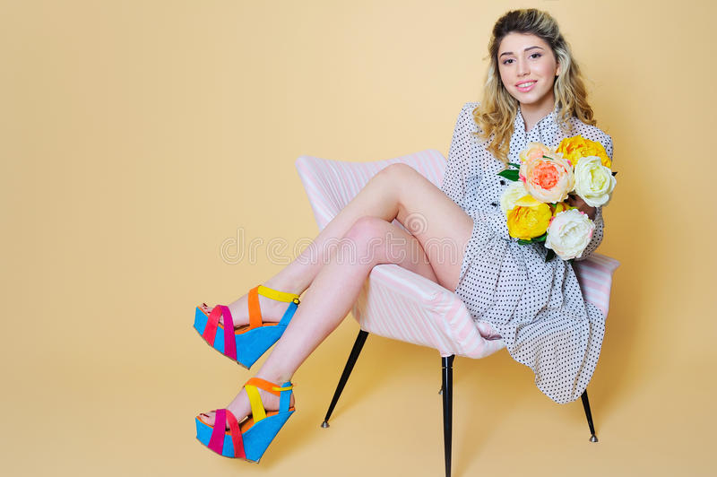 Beautiful woman portrait with flowers bouquet. Beautiful young woman posing with flowers bouquet on vintage chair royalty free stock photo