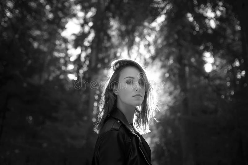 Beautiful woman portrait in a forest. With sunlight. black and white photo royalty free stock photography