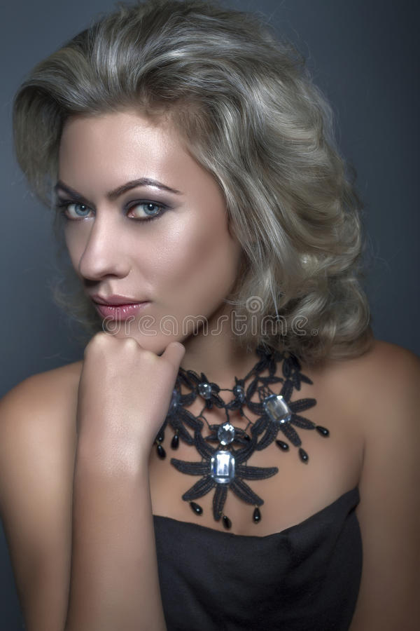 Beautiful woman. Portrait of a girl with a necklace royalty free stock images