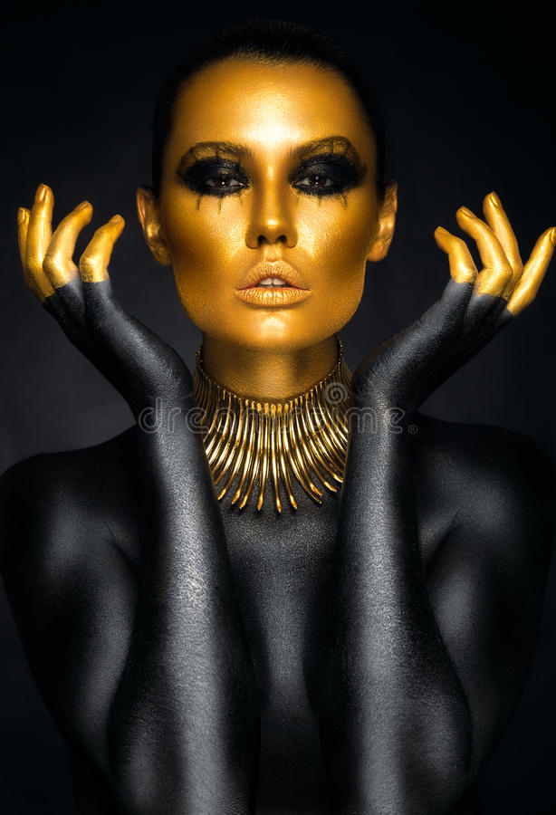 Beautiful woman portrait in gold and black colors. On black background stock photo