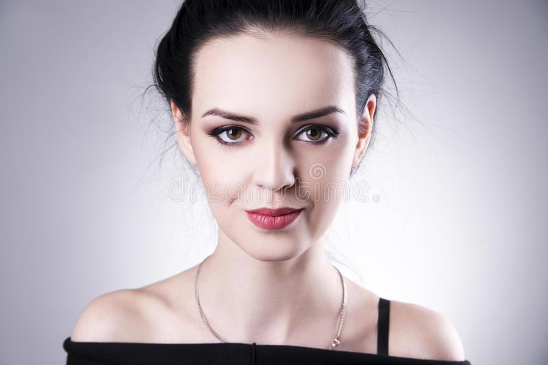 Beautiful woman portrait on a gray background. Professional makeup royalty free stock images