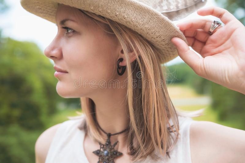 Beautiful woman portrait in hat with feather. Outdoor royalty free stock photos