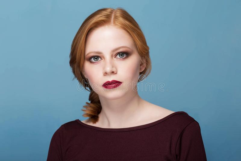 Beautiful woman in portrait. Redhead girl with a serious face. Looking at the camera royalty free stock photography